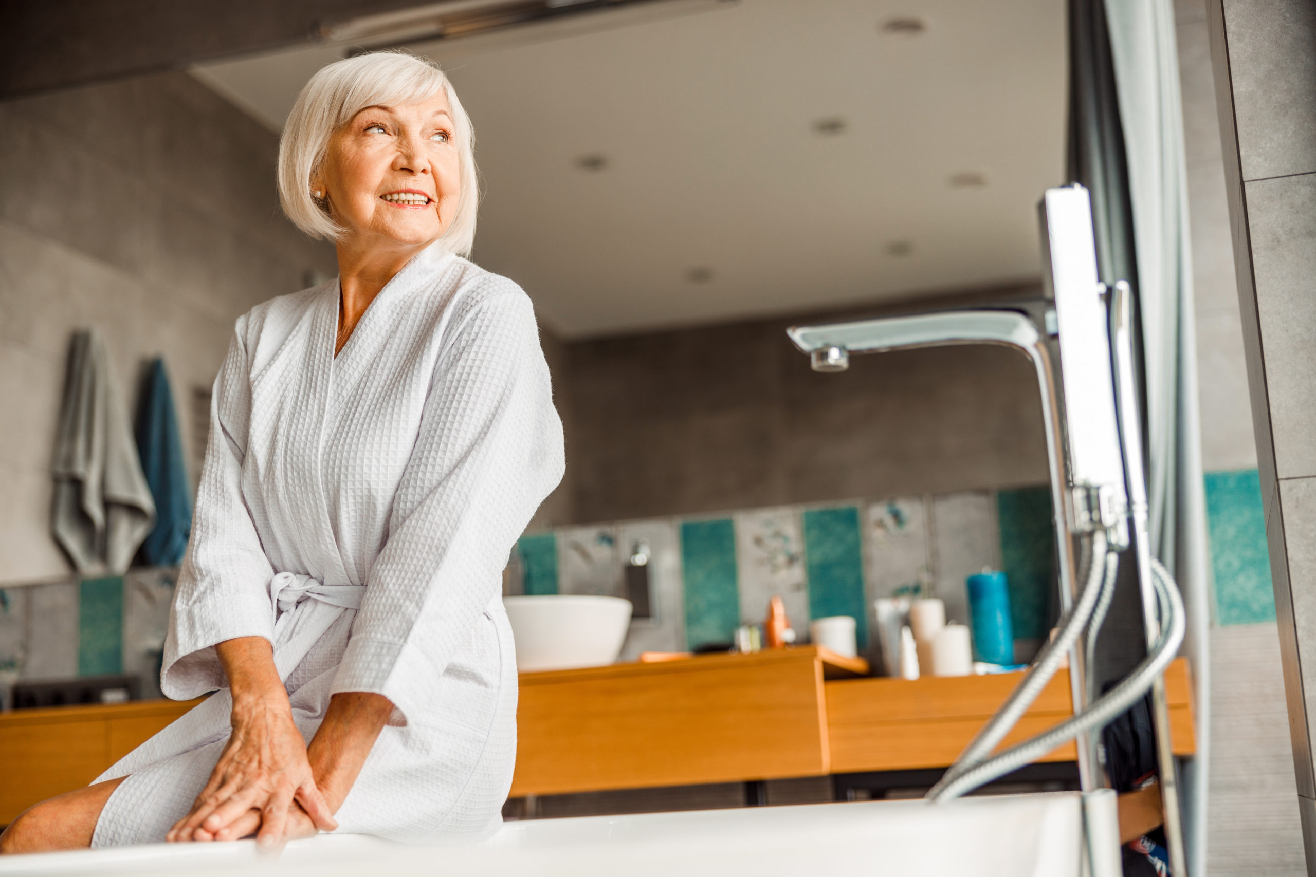 Smiling old lady in bathrobe sitting on the edge of bathtub stock photo