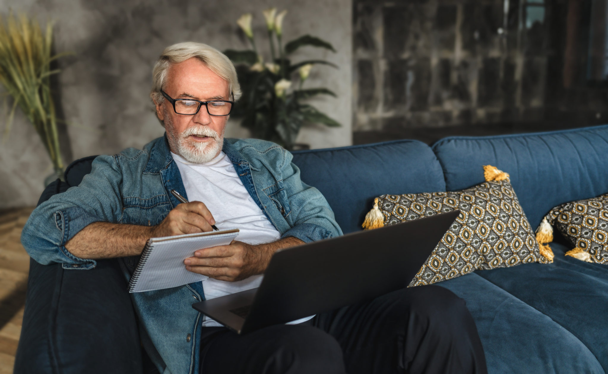 Focused elderly man writing notes in notebook watching webinar or online training using laptop computer, modern senior male with gray hair and beard learning online